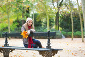 Sad girl sitting on a bench in park — Stockfoto