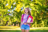 Cheerful college student holding books and folders — Stock Photo