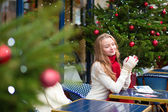 Girl writing Christma postcards in Parisian cafe — Stock Photo