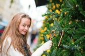 Girl decorating Christmas tree with candies — Stockfoto