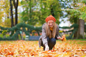 Cheerful young girl gathering autumn leaves — Stock Photo
