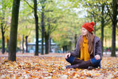 Girl sitting on the ground on a fall day — Stock Photo