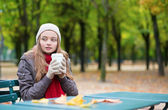 Girl drinking coffee outdoors — Stock Photo