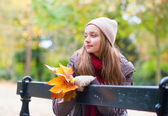 Girl sitting alone on the bench on a fall day — Stock Photo