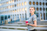 Young business woman drinking coffee outdoors — Stock Photo