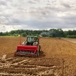 Tractors working on the field. - Stock Photo