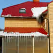 Icicles on the edge of a brick house. — Stock Photo #30663863