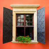 Open window with metal shutters on the red wall — Stock Photo
