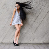 Beautiful brunette with long hair against a concrete wall — Stock Photo