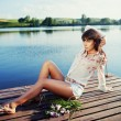Stock Photo: Beautiful brunette tanned girl sitting on a wooden pier