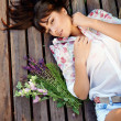 Beautiful brunette girl with a bouquet of wild flowers — Stock Photo