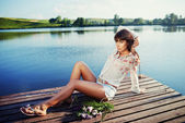 Beautiful brunette tanned girl sitting on a wooden pier — Stock Photo