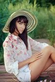 Doğa üzerinde rahatlatıcı şapkalı güzel esmer kız — Stok fotoğraf