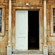Grungy old door of an old stone house with columns — Stock Photo #28081907