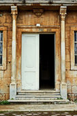 Grungy old door of an old stone house with columns — Stockfoto