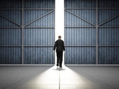 Man walks to large hangar doors — Stock Photo