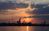 Sunset with silhouettes of cargo cranes in Odessa port,Black sea — Stock Photo