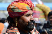 Rajput with bright turban and earring shows his moustache,Pushkar,India — Stock Photo