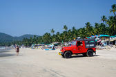 Life guard red car watching for tourists enjoying  Palolem beach,Goa,India — Stock Photo