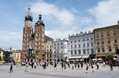 Tourists visiting main market square in front of St. Mary's Basilica, in Krakow, Poland — Stock Photo
