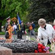 Old lady put flowers to Eternal Flame in commemoration of Soviet soldiers who fought against Nazi invasion during Second World War,Odessa,Ukraine — Stock Photo