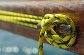 Closeup of old vintage snatch cleat with yellow line on wooden yacht, tool for keeping ropes tightened — Photo