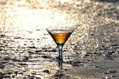 Martini glass in the surf — Stock Photo