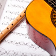 Wooden flute and classic acoustic guitar on sheet music. Close up. — Foto Stock