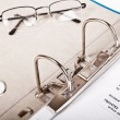 Glasses and open binder with invoice — Stok fotoğraf