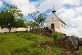 Small church with red roof and trees against blue sky — Stock Photo