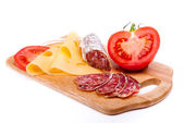 Salami, cheese and tomato on wooden board isolated on white — Stock Photo