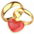 Gold wedding rings and red heart — Stock Photo