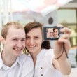 A young couple taking their photo on a digital camera — Stock Photo #13363632
