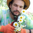 Man cutting the camomile bouquet - Stock Photo