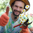 Man holding the camomile bouquet and the garden prune and showin — Stock Photo