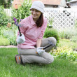 Young woman with rakes working in the garden bed — Stock Photo