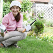 Stock Photo: Young woman with rakes working in the garden bed