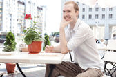 A young man sitting in a cafe — Stock Photo