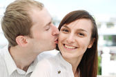 Portrait of young man kissing his girlfriend — Stock Photo