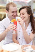 Young couple drinking juice in cafe — Stock Photo