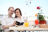 Young couple looking at menu in a small cafe — Stock Photo