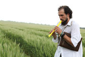Man playing flute for good wheat year — Stock Photo