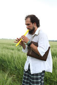 Man playing flute for good wheat year — Stok fotoğraf