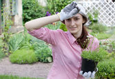 Tired woman with seedlings in the garden — Stock Photo