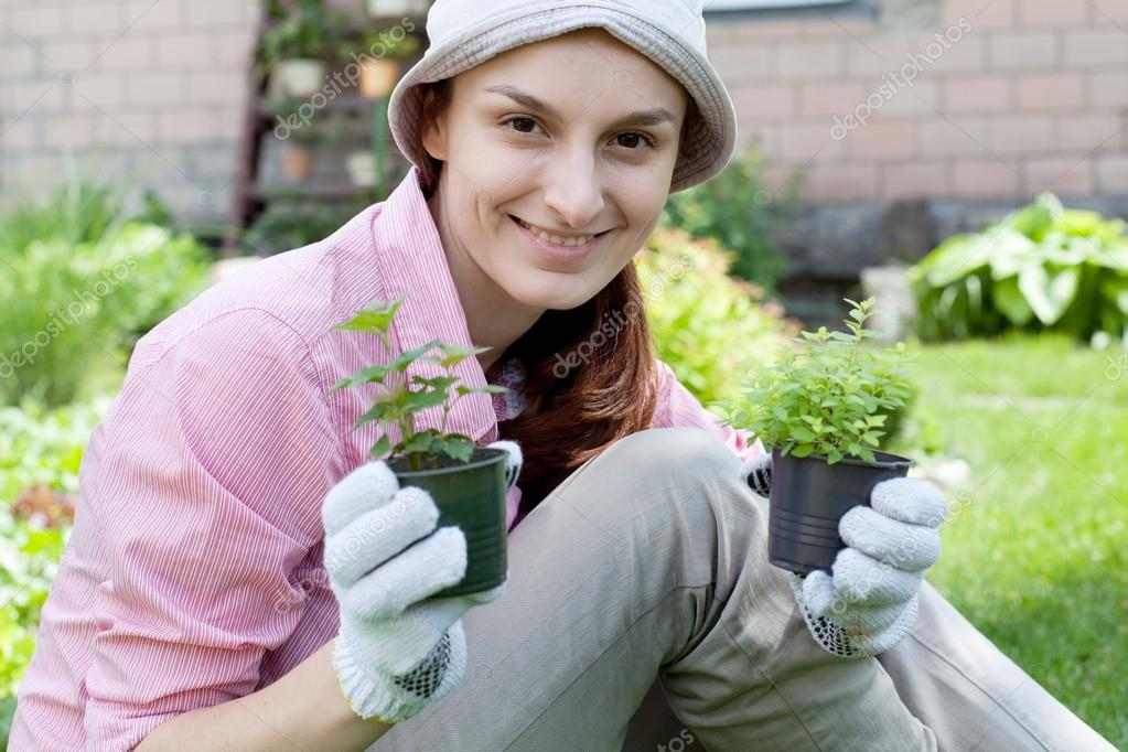 Smiling woman with herbs in garden — Stock Photo #13363857