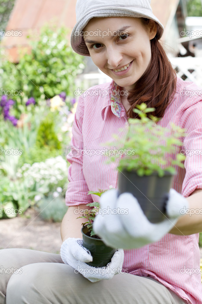 Smiling woman with herbs in garden  Stock Photo #13363860