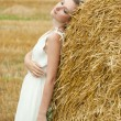 Stock Photo: Cute young female posing by a farm