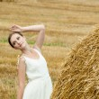 Woman on a hay in a field outside the city — Stock Photo #13733508