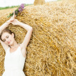 Stock Photo: Woman on a hay in a field outside the city