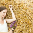 Woman on a hay in a field outside the city — Stock Photo